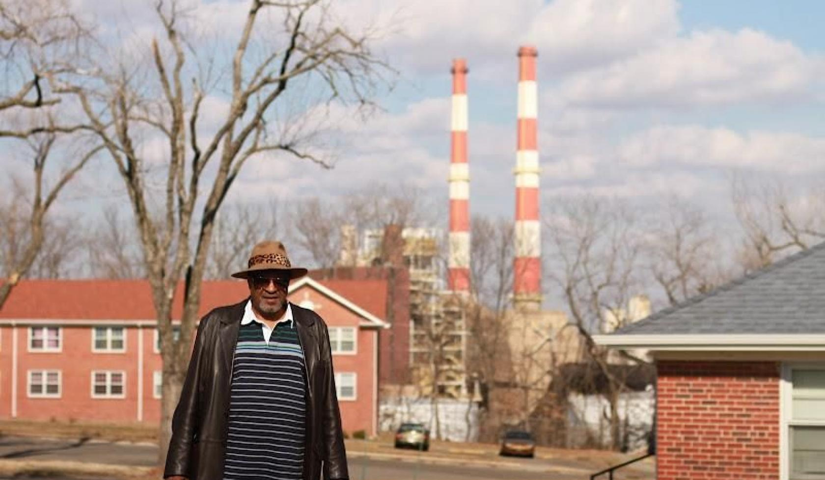 A man stands in the foreground of a neighborhood with brick multifamily buildings and smoke stacks on the horizon.