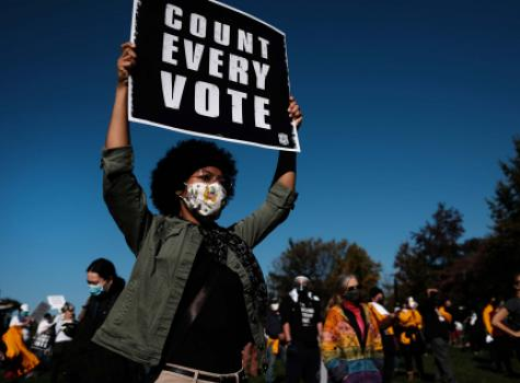 Black Female holding Voting Sign - Group in background - wearing face mask