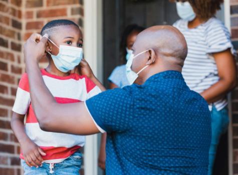 Black Man Helping a Child Put on a Mask