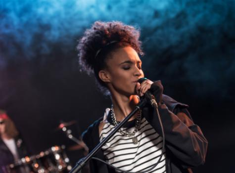 Black Performer Singing into Microphone on Stage