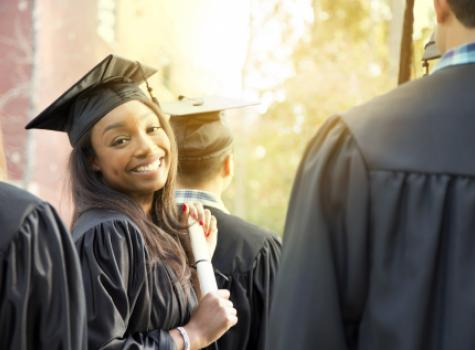 Close-up of Black Female Graduate Smiling at Camera Amongst Group of Fellow Students